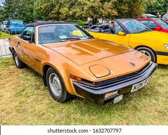 Tichborne, Hampshire, England September 7 2019. Parked Triumph TR7 Roadster in golden orange with black trim.