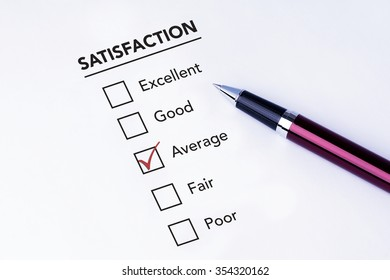 Tick placed in average check box on service satisfaction survey form with a pen on isolated white background. Business concept survey.