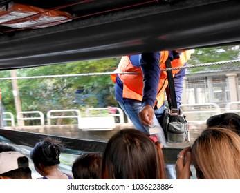 ticket taker wear orange life jacket is working on the public boat, Bangkok, Thailand, Jan 11,2018