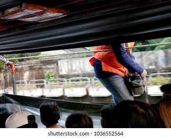 ticket taker wear orange life jackets, he is working on the boat motion on canal with passengers, Bangkok, Thailand, 11 Jan 2018