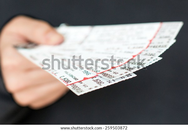 Tickets being held in a hand.