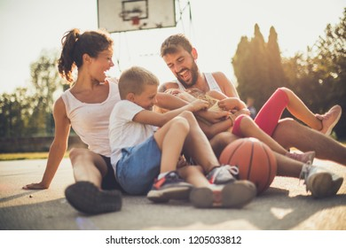 Tickling attack. Family on basketball playground.