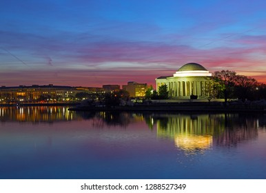 Tidal Basin panorama at dawn with Thomas Jefferson Memorial during cherry blossom festival in Washington DC, USA. Colorful reflection of buildings in calm water of the Tidal Basin reservoir.