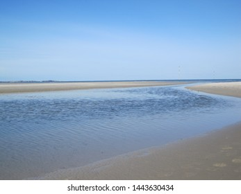 Tidal creek on the beach near Norddorf (Amrum, Schleswig-Holstein, Germany) with the island Sylt in the background