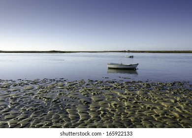 Tidal flat with small boats on a lagoon and water, mud and sand