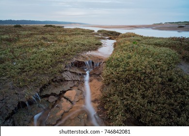 Tidal salt marsh creek on the North Norfolk coast at Holkham as the seawater starts to drains out towards low tide.