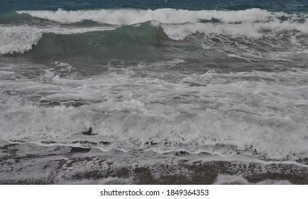 The tide crashes in against the rocks. Spray is tossed upwards and foam rides on top of the waves as they approach the shore.