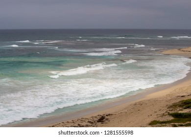 Tide ebbing out from the famous white sandy surfing beach and rocky shore  at Margaret River South Western Australia  on a calm cloudy afternoon in early summer  creates a scenic seascape.