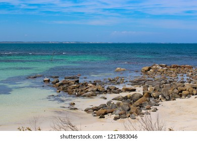 Tide ebbing out from the  white sandy surfing beach and rocky shore at Margaret River South Western Australia on a calm cloudy afternoon in  early summer  creates a scenic seascape.