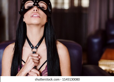 Tide and painful. Beautiful young woman in black underwear adjusting her bondage while sitting in the chair indoors