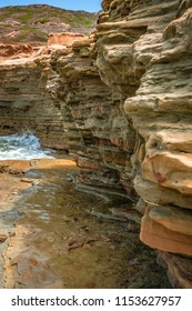 Tide pool walls at low tide and layers of rock and sandstone.