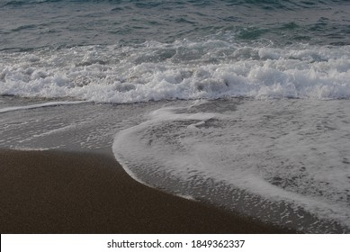 The tide rides over the last rocky hurdles and reaches the shore as a mass of foam.