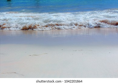 The tide and a wave at the start of its run up the sand towards the beach.