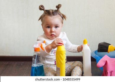 Tidy up concept, stay home, child playing with bottles with household chemicals sitting on the floor of the house