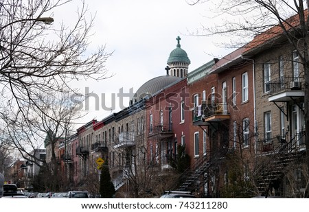 A tidy row of row houses in Mile End neighborhood in Montreal Quebec Canada with a religious building behind