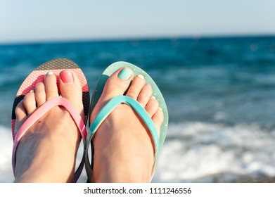Tidy woman feet with multi-colored pedicure in slippers on summer pebble beach. Vibrant outdoors horizontal inspirational close-up image with blue seascape background.