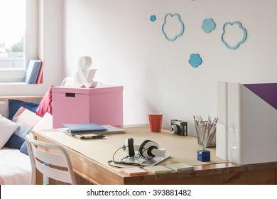 Tidy wooden desk in teenage girl's study room