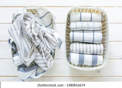 Tidying up concept - folded kitchen linens in white basket, top view