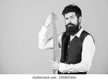 The tie is both stylish and elegant. Stylish businessman. Bearded man holding stylish necktie. Brutal guy wearing stylish clothes and accessory. Fashion model in trendy hipster style, copy space.