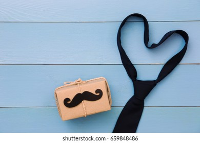 Tie, gift box, paper mustache on wooden background with copy space. Greetings and presents. Happy Father's Day.