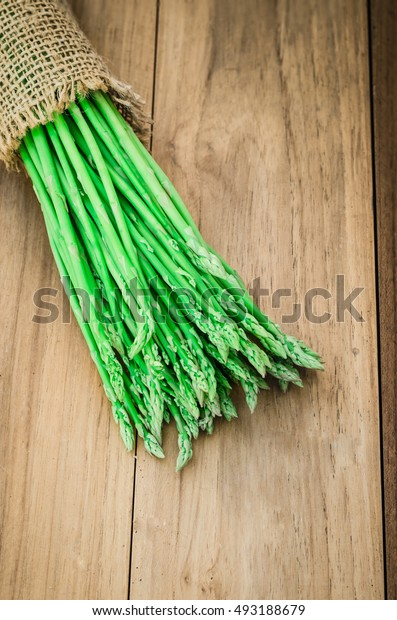 tied asparagus on old wood table, a green plant use for food, vegetable