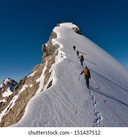 Tied climbers climbing mountain with snow field tied with a rope with ice axes and helmets