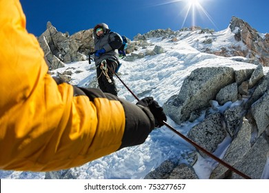 Tied climbers climbing mountain with snow field tied with a rope with ice axes and helmets first person.