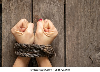 tied female hands with rope on wooden background close up