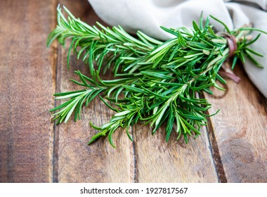 Tied fresh organic rosemary herb on the wooden background. Top view rosemary fresh from the garden.