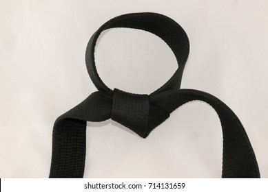 Tied martial arts black belt isolated on an off-white background