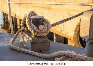 Tied rope knot on metallic bollard , seafaring port. Nautical ship moored in dock. Anchor rope in the port, ship mooring tool. - Shutterstock ID 1815545354