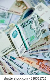 tied with a rubber band russian banknotes stands on money background