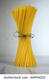 Tied spaghetti pasta on a white rustic surface