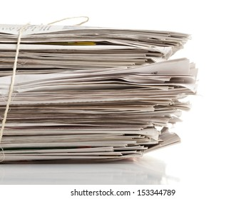 Tied up stack of old newspapers collected for recycling on white background