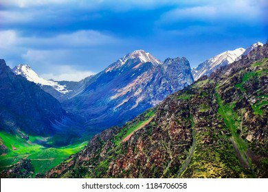 Tien Shan range. Amazing scenic view, rugged colorful rock, green valley against the background of high mountain tops covered with snow and dark evening sky, Bishkek - Osh highway, Kyrgyzstan,