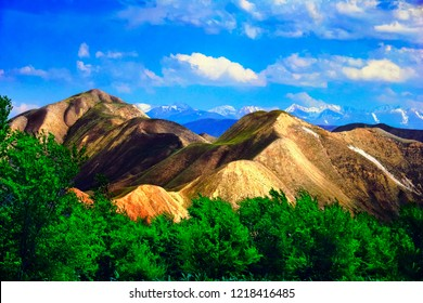 Tien Shan range. Beautiful scenic view, barren sandy mountains  and green wood against the background of distant high mountain tops covered with snow and cloudy sky, Bishkek - Osh highway, Kyrgyzstan