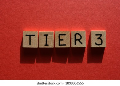 Tier 3, coronavirus alert levels, word in wooden alphabet letters isolated on red background - Shutterstock ID 1838806555