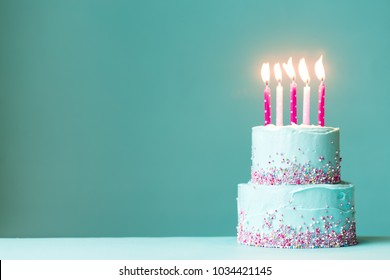 Tiered birthday cake with pink candles and sprinkles