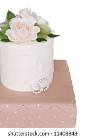 Tiered wedding cake decorated with two rings, and roses.