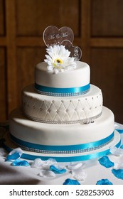 Tiered white wedding cake against traditional wooden panel background with blue ribbon and flower petal decorations