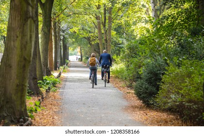 Tiergarten city park, autumn, Berlin, Germany. View of a mature couple riding bicycles