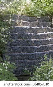 Tiers of screened in Gabion riprap (rock) lining a stream preventing bank erosion