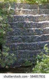 Tiers of screened in Gabion riprap (rock) lining a stream for controlling bank erosion