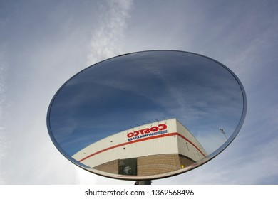 Tigard, Oregon - Mar 15, 2019: The sign of Costco Wholesale seen from a traffic safety mirror at a Costco Wholesale store.