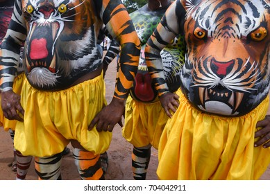 Tiger dance in procession during harvest festival Onam, Kerala, India. Many Indian men, body painted artist  in disguise of tiger with mask at Thrippunithura, Kerala South India.