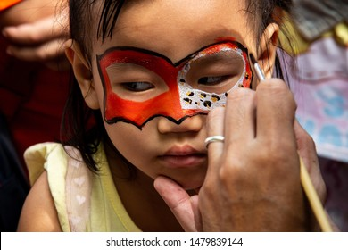 TIGER KINGDOM, CHIANG MAI, THAILAND - JULY 29, 2019: Artist paints batman mask on unidentified young Asian girl on International Tiger Day July 29, 2019 in Tiger Kingdom Chiang Mai, Thailand.