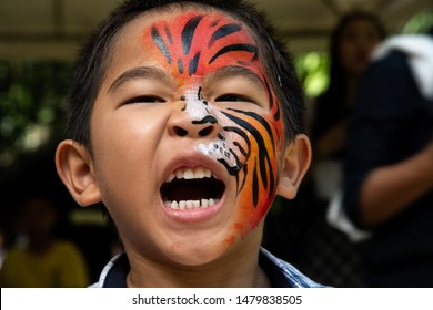 TIGER KINGDOM,CHIANG MAI,THAILAND - JULY 29,2019: Unidentified young Asian boy paints tiger on his face during visiting Tiger Kingdom on International Tiger Day on July 29,2019 in Chiang Mai,Thailand.