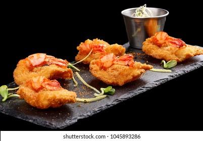Tiger prawns in batter. Ebi tempura with spicy sauce on dark background