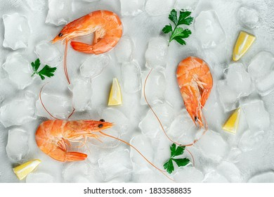 Tiger shrimps with ice, lemon and parsley. Food background. Flat lay, top view