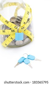 Tight financial budget concept with coins, measurement tape and padlock isolated on white background